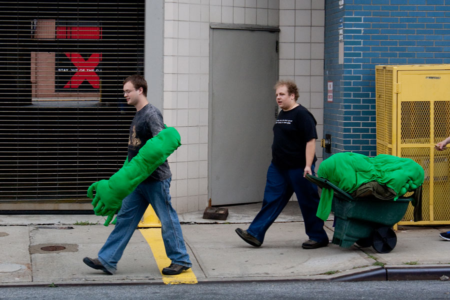 Photo of one guy wearing enormous hulk arms with the rest of his costume dragged on a cart by his friend.