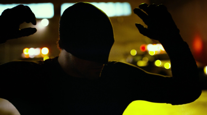 Matt is cornered by police and sticks his hands in the air, as seen in episode five of Marvel's Daredevil on Netflix