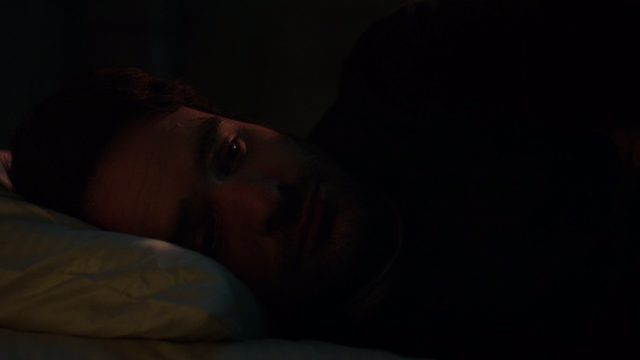 Matt looking infinitely sad while on his bed listening to sirens in the background, as seen on Marvel's Daredevil season three, episode one.