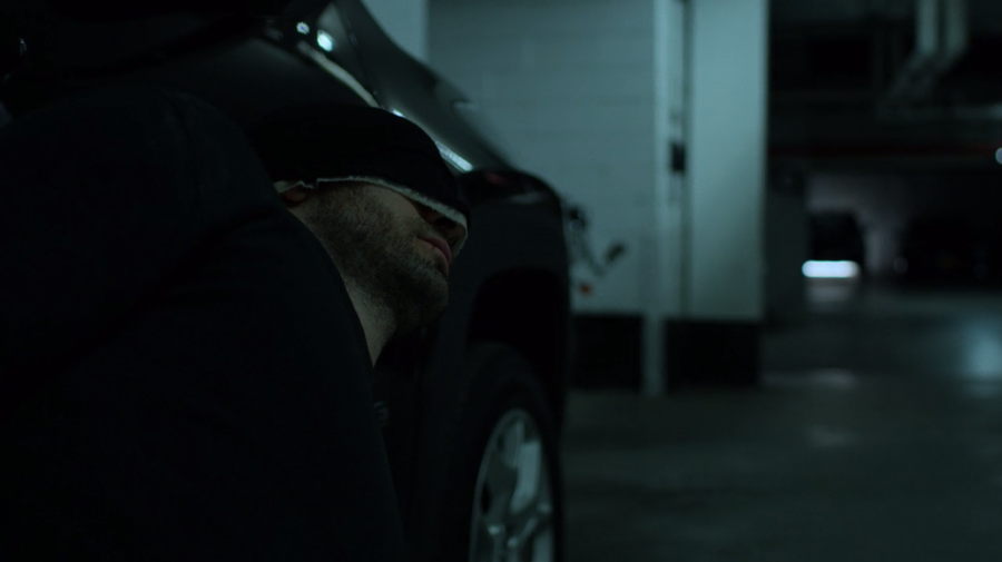Matt hides behind a car in the hotel parking garage, as seen in Marvel's Daredevil, season three episode three